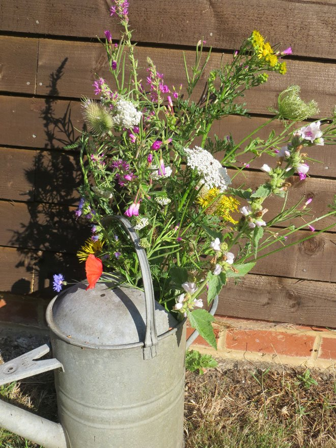 Watering can filled with wildflowers for a summer wedding